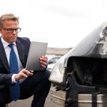 Lawyer Looking at Car Damage from a Car Accident